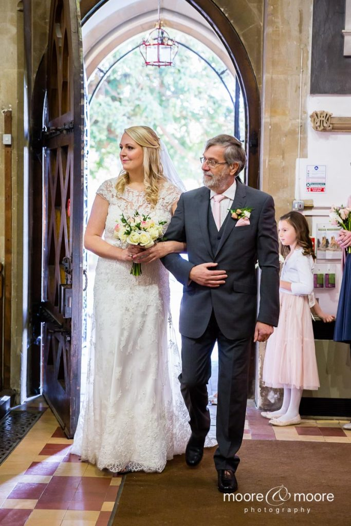 Bride entering the church with her father, photographed by Wedding Photographers Hampshire, moore&moore photography